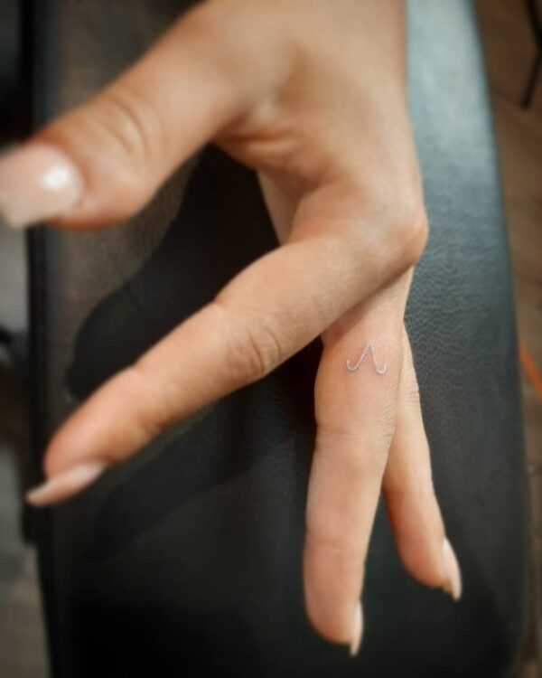Aries White Ink Symbol Finger Tattoo
